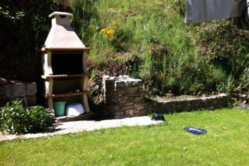 El pequeño jardín de la casa donde además de la colada y tendedero, tienen barbacoa.